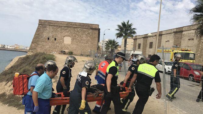 Varios bomberos, policías locales y sanitarios trasladan al herido en una camilla.