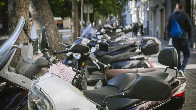 Multas asomando por los manillares y sillines de las motos que amanecieron ayer aparcadas en la plaza de Mina.