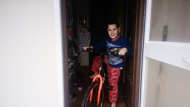 Un chaval con su nueva bicicleta en la puerta de su casa.