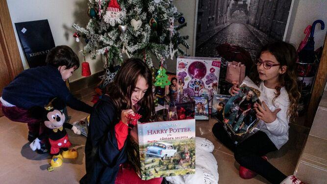 Dos niñas muestran sus juguetes junto al árbol de Navidad.
