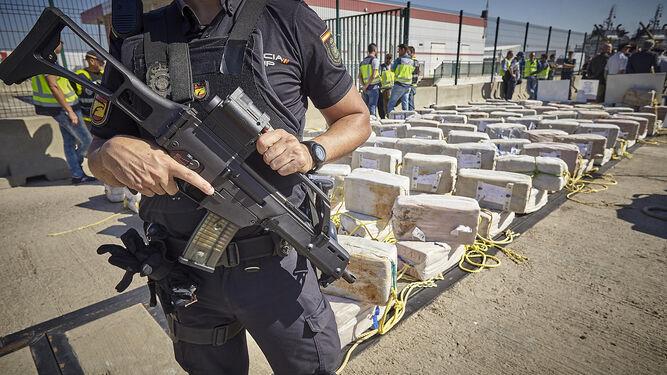 Un agente de la Policía Nacional custodia el alijo del buque 'Thoran', intervenido en octubre de 2017 y descargado en el puerto de Cádiz.