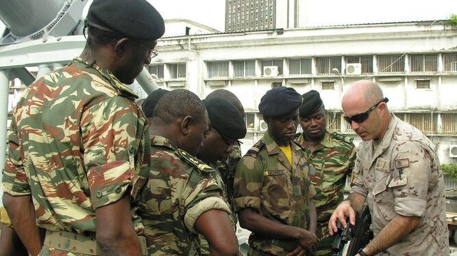 Un infante de Marina español instruye a soldados cameruneses en las características de un fusil de asalto.