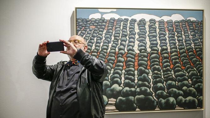 Un espectador fotografía algunos de los paisajes de Eugenio Chicano ante la impresionante obra de los olivares de Jaén.