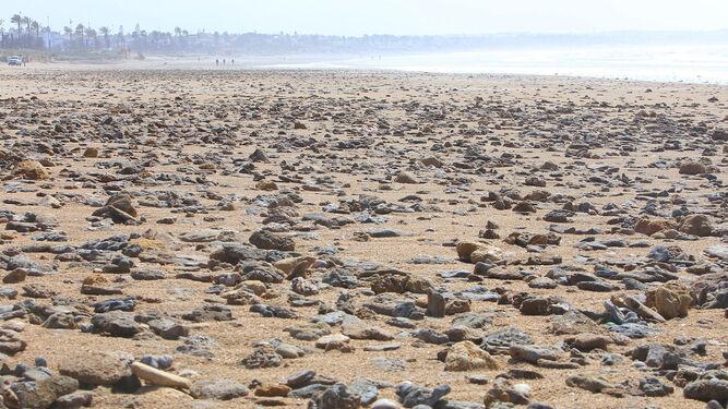Aspecto que presentaba ayer la primera pista de la playa de La Barrosa, repleta de piedras y rocas.