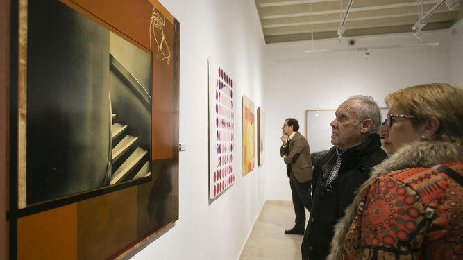 Algunos visitantes observan las obras de la exposición en la sede de Cajasol.