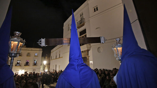 Momento en que la Cruz de Guía del Perdón hace su salida por la puerta de Santa Cruz, con la plaza de Fray Félix llena de público.