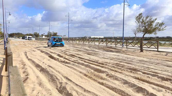 Un vehículo atraviesa con dificultad la zona afectada por la arena, ayer al mediodía.