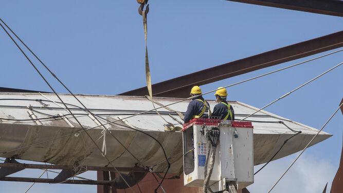 Los operarios manejan las cinchas con las que sujetan la estructura.