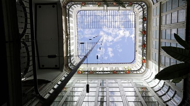 Torre de ascensor en el patio de una finca cubierta de vidrio espejado.