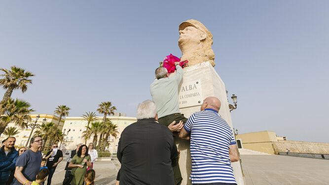 Juan Mesa, de la peña Paco Alba, ayudado por Eugenio Mariscal y Agustín Rubiales para colocar flores en el busto.
