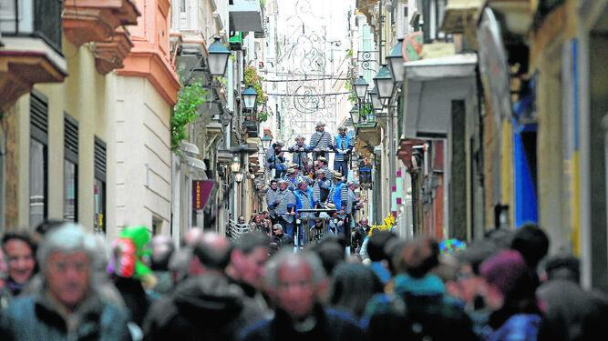 Una calle repleta de público para escuchar un coro en Carnaval.