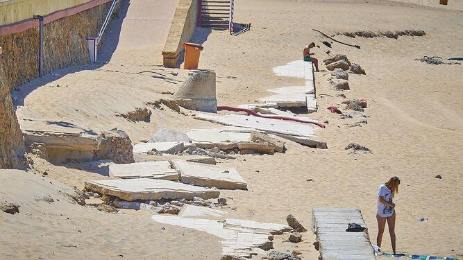 Aspecto que presentaba ayer la playa de Santa María del Mar, en Cádiz, a la altura del emisario submarino, cuya estructura afloró con el temporal.