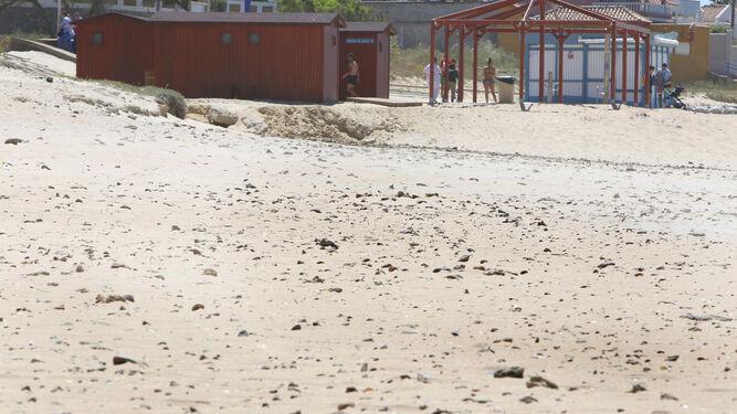 Piedras a la vista por la falta de arena en la playa de La Barrosa, a la altura de la segunda pista.