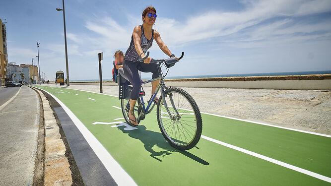 Una ciclista se traslada con su hijo por el carril bici que atraviesa el Paseo Marítimo./JULIO GONZÁLEZ