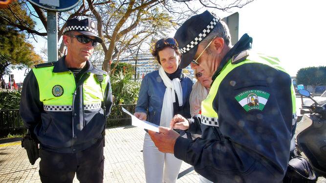 Dos agentes de la Policía Local atienden a una ciudadana.