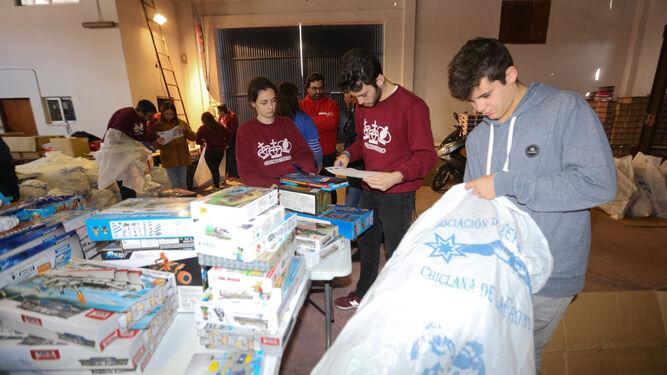 Los voluntarios clasifican y empaquetan los juguetes en una nave situada en el polígono de El Torno.