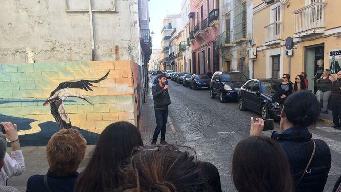 El autor del mural de las cigüeñas, explicando los detalles de su obra.