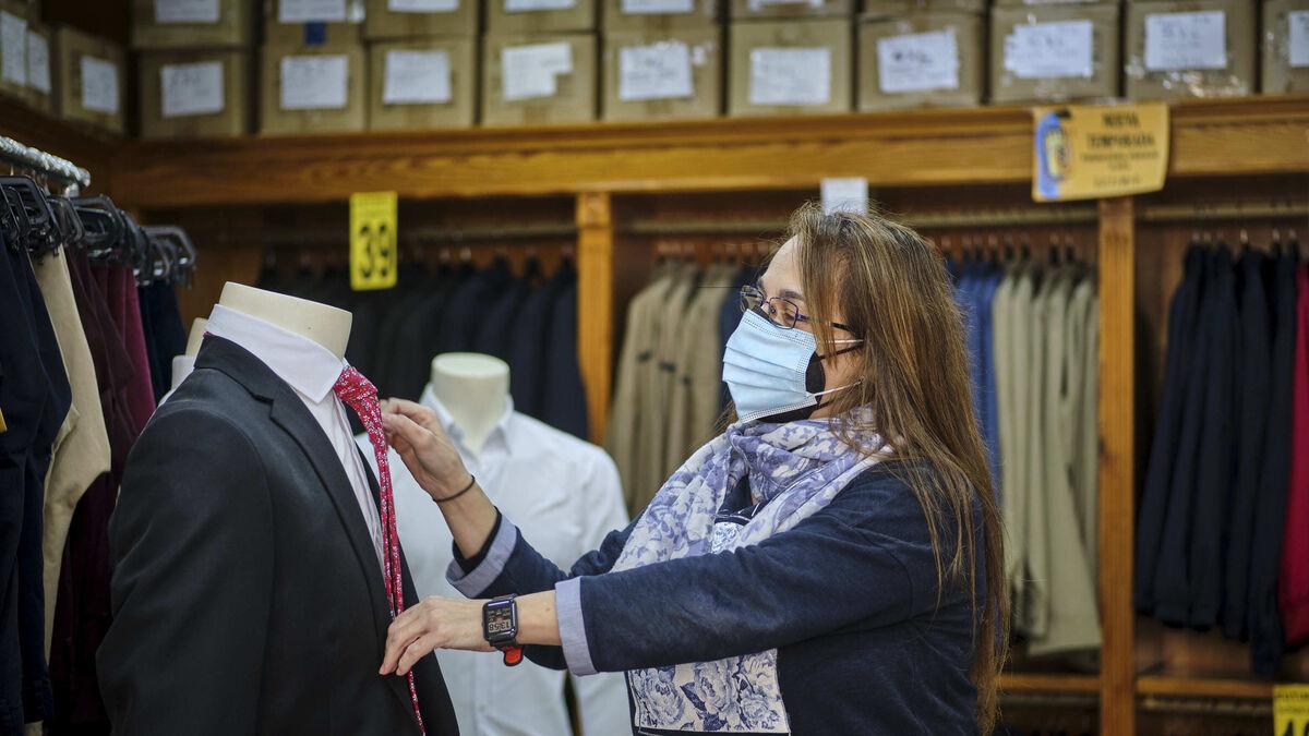 María del Carmen Domínguez anuda una corbata en Modas Eutimio.
