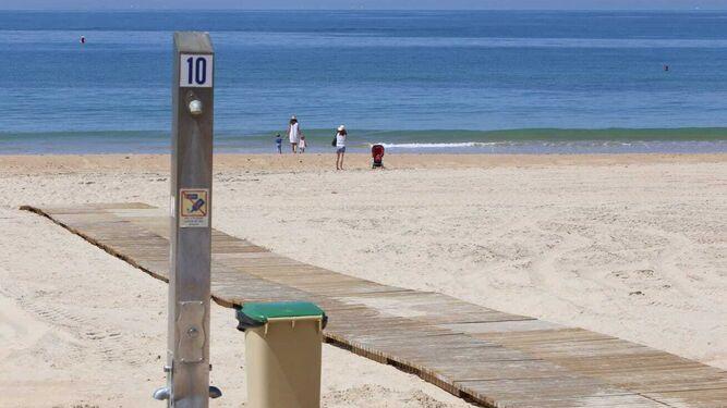 Vista de la playa de La Barrosa con algunas personas paseando             por la orilla